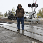 David Peck photo     Deaver mayor Bill Camp stands at the railroad crossing leading into the community that local residents have been trying to get BNSF to repair for several years now.