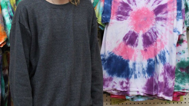 Sam Smith photo Aaron Snyder poses beside a display of tie-dye shirts at his new business, the Astral Attic Space, in Lovell. The store will have tie-dye shirts, thrift store items, beverages, games and much more.