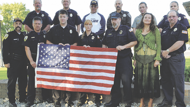 file photo      Posing with the Stuart Yates flag in 2011 are (back row, l-r) LPD Chief Nick Lewis, Randy Davis, Frankie Rohrer of the Byron PD, Steve Coleman of the Big Horn County Sheriff's Office, David Baker of the National Park Service, dispatcher Mandy Martin, (front) LPD officers Greg Hess, Noe Garcia, Matt Koritnik and Jessica Flood and dispatchers Aaron Harris, Kimber Allen and Ron Salyer. See more in excerpt from 10 years ago.