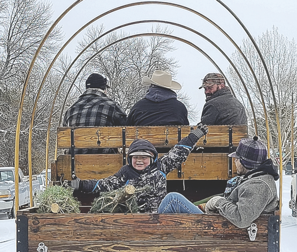 Wade Hill (left) and Chase Lewis (right) enjoy a ride as (l-r) Jerry Hill, Mike Apanashk and Caleb Norris drive a wagon during their Cowboys for Christmas delivery in Lovell. courtesy photo