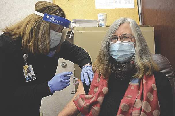 Mary Freund, a nurse practitioner at Three Rivers Health, gets the first dose of the COVID-19 vaccine from Linda Walker.  Nathan Oster photo