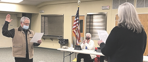 David Peck photo     Town of Lovell clerk/treasurer Valerie Beal swears in newly appointed councilman Ray Messamer Tuesday night at the community center. Seated at the council table behind them is council member Carol Miller.