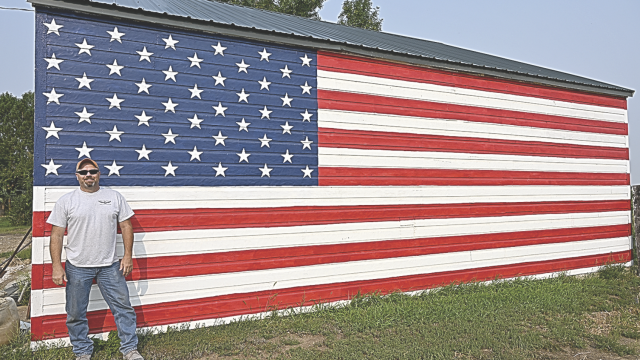 David Peck photo     Kevin Reece stands in front of the 30-foot American flag he painted on the side of a building at his home west of Cowley in July. He says the work has attracted a lot of positive attention from passers-by and local residents.