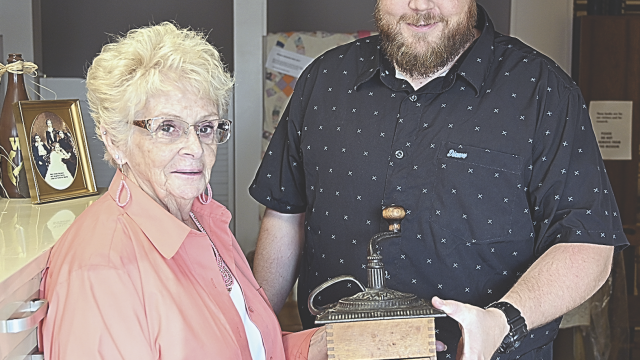 David Peck photo     Jed Nebel, right, presents a coffee grinder once owned by Caroline Lockhart to Karen Spragg, president of the Lovell-Kane Area Museum board of directors. The item is on loan from the Nebel family to the museum.
