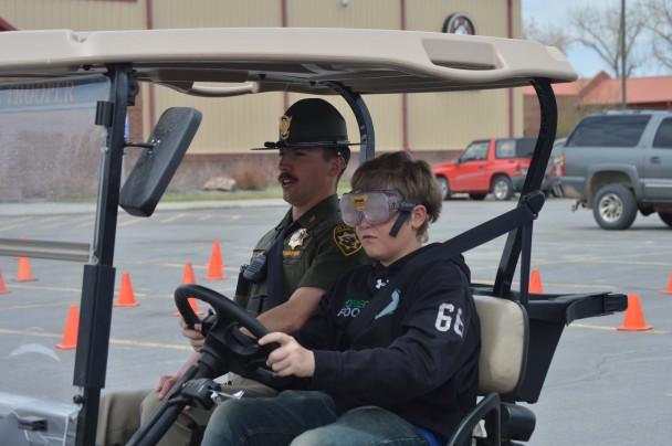 Barbara Anne Greene Joseph Stanworth and WHP Trooper Jason Roascio finish a DUI simulation at the Burlington Schools.