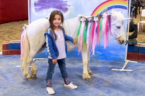 Winter Marchant of Greybull poses with a unicorn at the Circus in Basin Friday.
