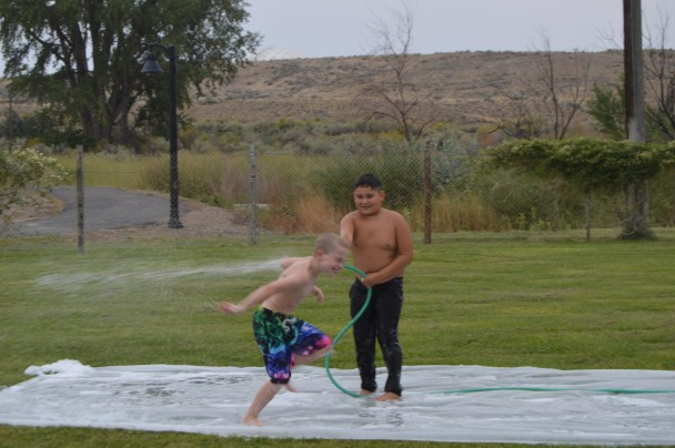 Barbara Anne Greene Daniel Stamstad of Greybull squirts Detrich Otto of Basin on the huge slip and slide that was set up for Family Fun Day in Basin.