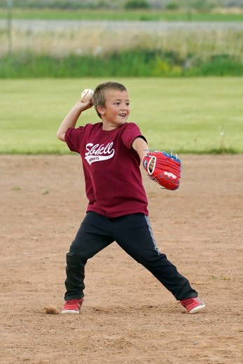 Lisa Kunkel Six-year-old Trapper Triplett, of Basin, winds up to throw to first base during Tuesday night's coach-pitch game in Otto.