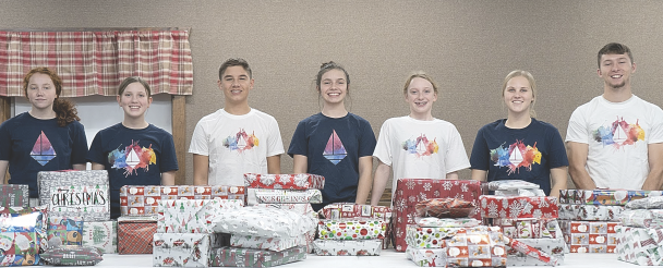 Members of the Who We Are youth staff are (l-r) Connie Hall, Keyanna Walker, Braxton Felkins, Danika Crumrine, Becca Nichols, Chevy Jolley and CJ Pickett, posing here with presents they had assembled for distribution at Christmas.