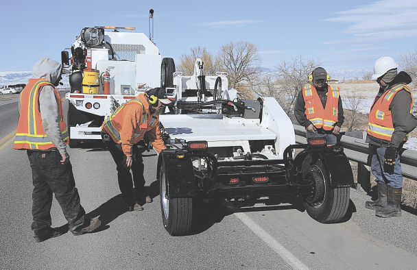 David Peck photo     S&L Industrial and MRL Equipment workers adjust S&L's new rumble strip machine for a new stretch of highway during the machine's training and test run between the Oasis Junction and Cowley Tuesday afternoon.