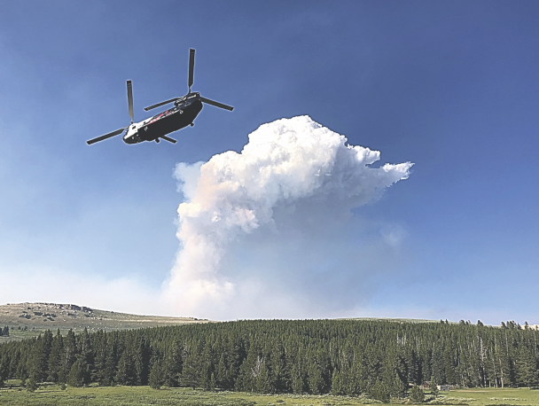Bob Mangus photo     A firefighting helicopter flies north after taking on water from a pond atop the Big Horns to battle the Crater Ridge fire Sunday afternoon.