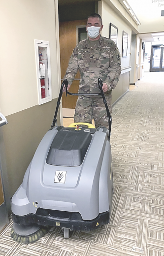 David Peck photo     Sergeant Mike Jones vacuums a hallway, one of the many odd jobs three  National Guardsmen assigned to North Big Horn Hospital are undertaking to help assist the staff.