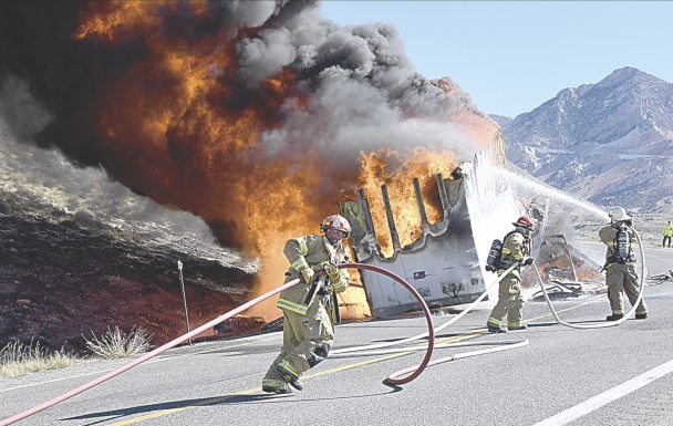 David Peck photo     Lovell volunteer fireman Michael Jameson drags a fire hose uphill to assist Seth Mayes (center) and Lynn Hitz as they battle the Saturday morning truck fire 20 miles east of Lovell on U.S. 14A.