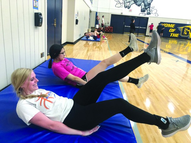 Kelsie McColloch and Ashley Gomez work on their ab strength during Tuesday afternoon's practice at GHS.