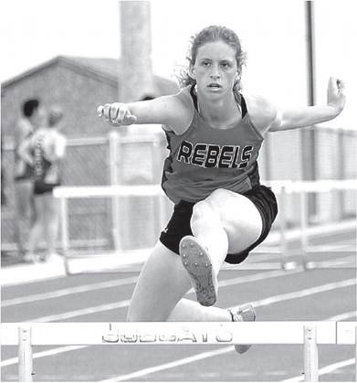 Sam Smith Lady Rebel senior Breana Riley clears the hurdle during the 300-meter hurdles at the Bobcat Invitational Saturday in Thermopolis. Riley placed 10th in the event with a time of 54.96 seconds.